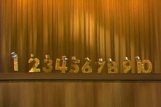 Number One leads the singing numbers. Each of the numbers has a hat on top. Numbers sing One. Sesame Street 123 Count with Me