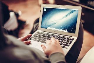 膝の上でMacを操作している写真