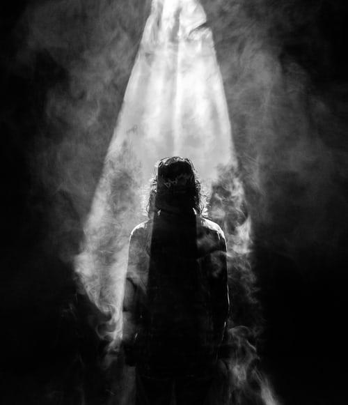 Mujer mirando un foco de luz que viene del cielo. Será el alma de las personas