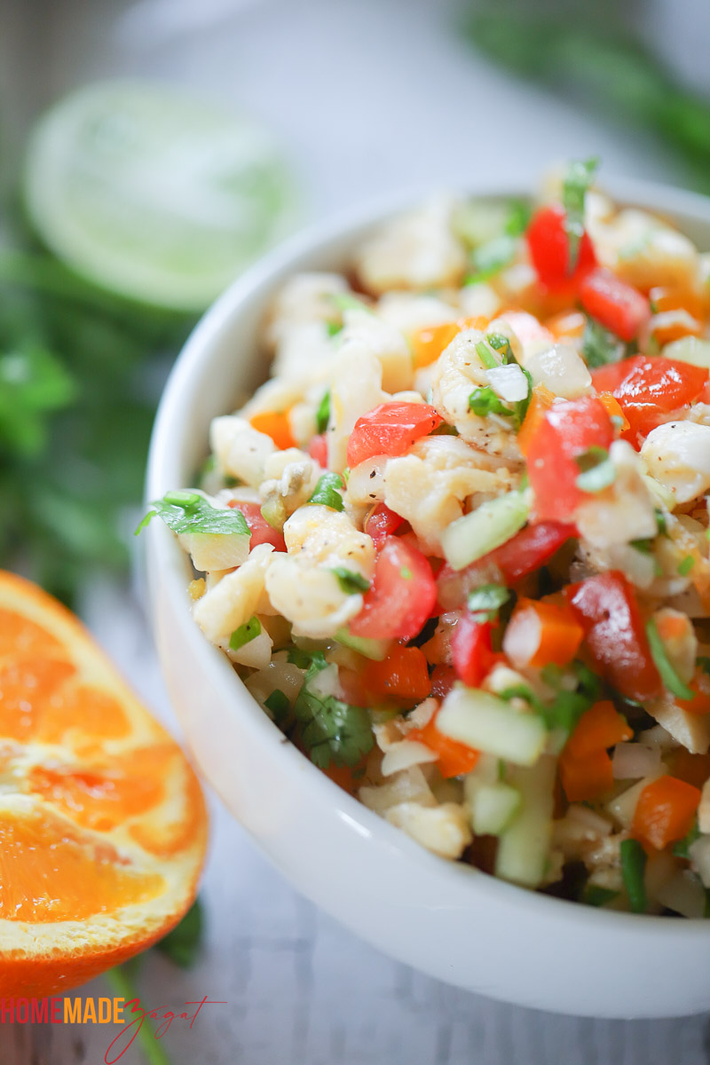 Bird's eye view of a bowl of conch salad with orange on the side