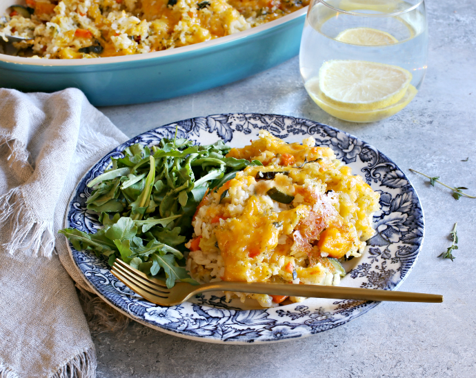 Recipe for a cheese topped rice casserole cooked with onions, carrots, zucchini and butternut squash.