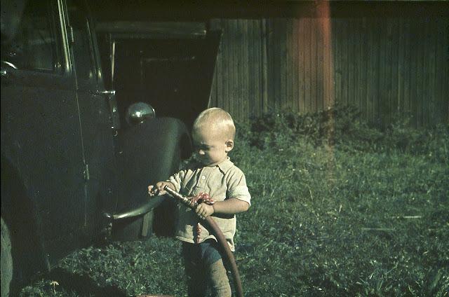 Värikuva. Pieni poika seisoo auton etupuolen edessä, puutarhaletku kädessään.