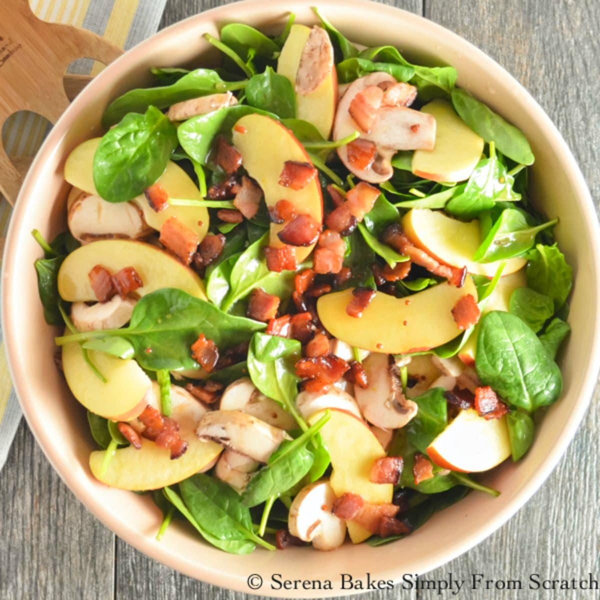 Spinach Salad with bacon, fuji apples and a homemade honey mustard dressing. The flavor combination is delicious from Serena Bakes Simply From Scratch.