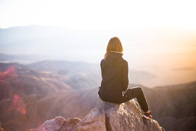 woman watching sunrise on a trip