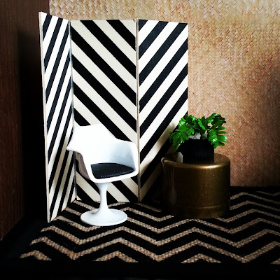 One-twelfth scale modern miniature scene including a plywood screen with black stripes, a hessian rug with a black chevron pattern, a white tulip chair with a black seat and a bronze side table with a potted fern sitting on it.