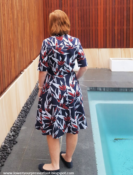 photo of a woman in a blue and red floral dress posing next to a swimming pool