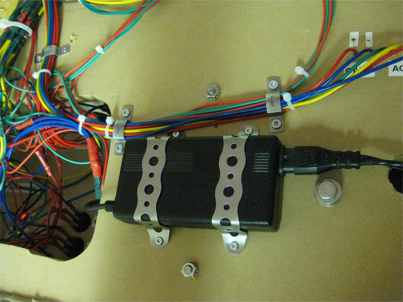 A 12 volt AC inverter attached to the bottom of a model railroad control panel with metal brackets
