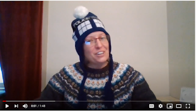 A white woman with glasses wears a knit hat with a Dr. Who Tardis design and a multi colored sweater