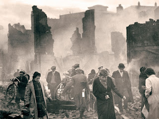 Black and white people wandering around in smoky rubble.Aftermath of World War II, France