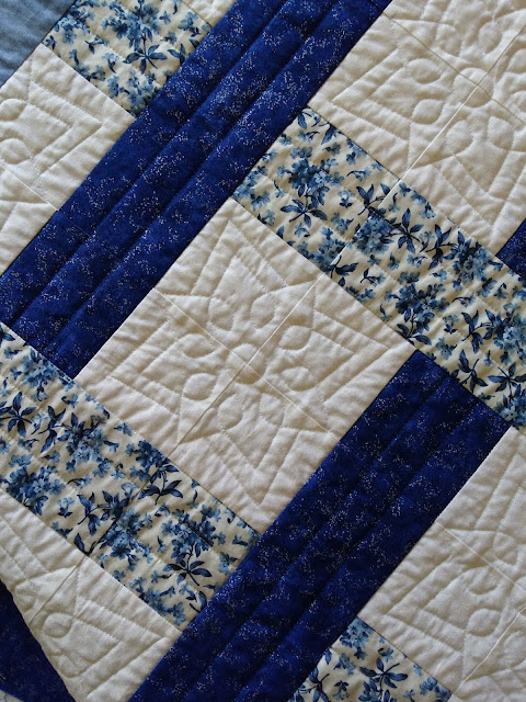 Detail of straight line quilting and bloom motif on blue and white patchwork quilt