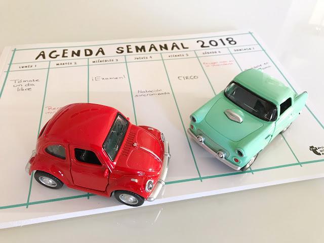 Coches de juguete (uno rojo y uno verde) encima de una agenda
