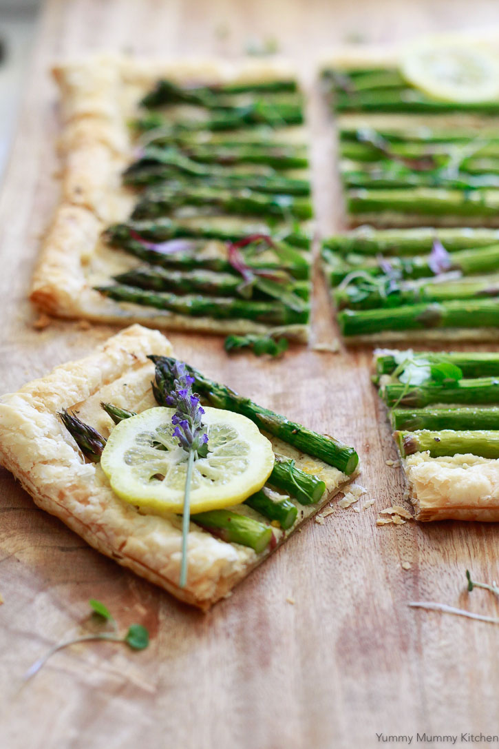 A piece of asparagus tart on puff pastry with a slice of lemon and microgreens. This beautiful asparagus tart is perfect for spring parties.