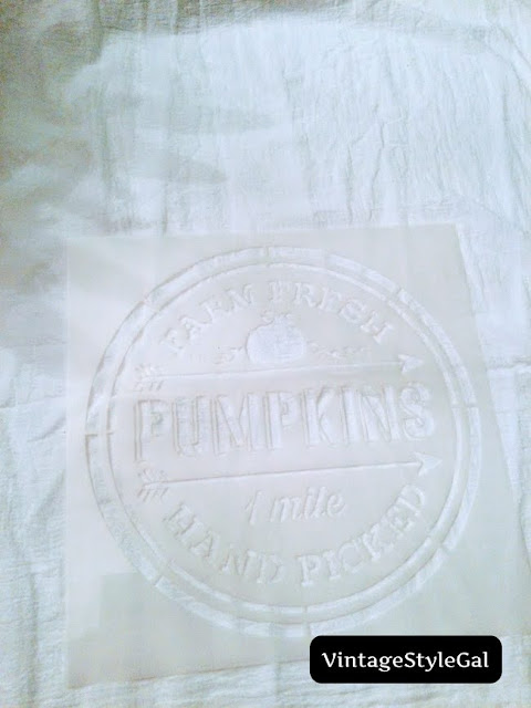Flour sack towel laying flat with stencil on top of towel