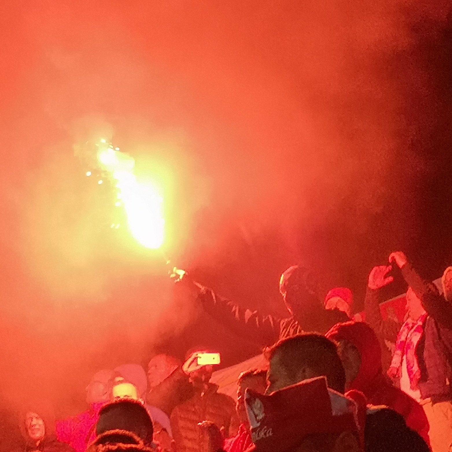 Poļu futbola fans maskā un ar dūmu sveci rokā