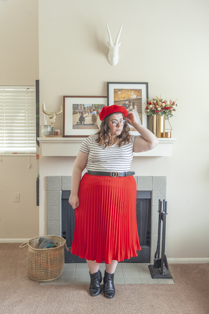 An outfit consisting of a red beret, white and black striped tee tucked into a red pleated midi skirt and black chelsea boots.