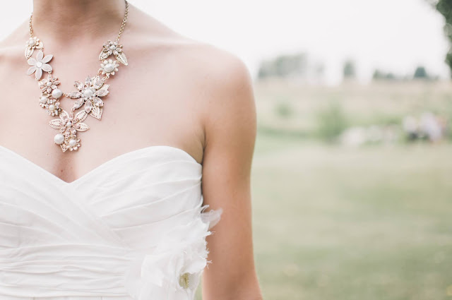 A medium shot of a woman in a strapless white dress while wearing a intricately-detailed necklace.