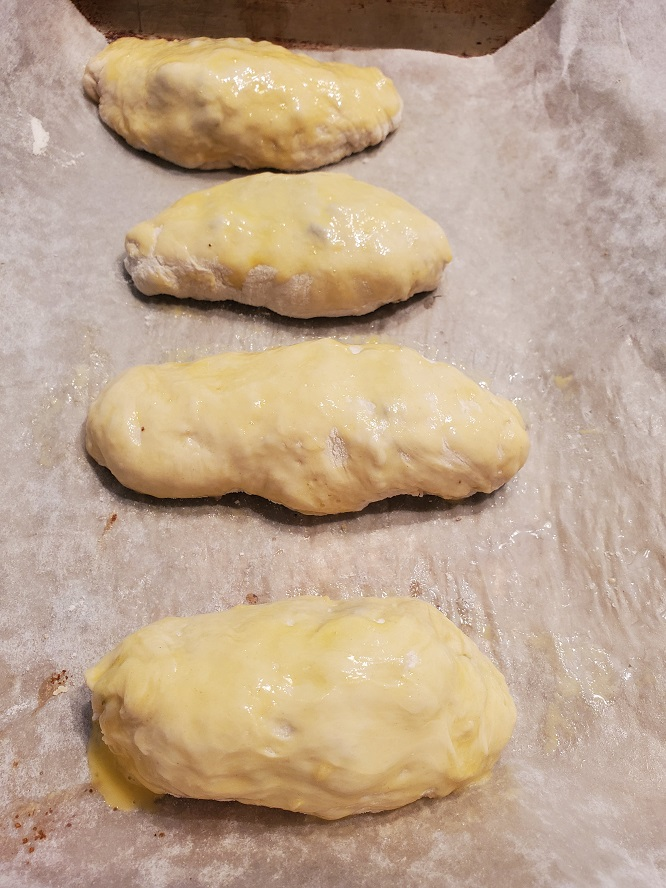 these are raw runza bundles on parchment paper ready to be baked on a cookie sheet