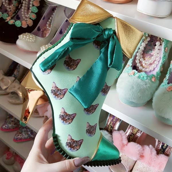 green ankle boot in hand with shoe shelves behind and cat print uppers and jewel shaped heel