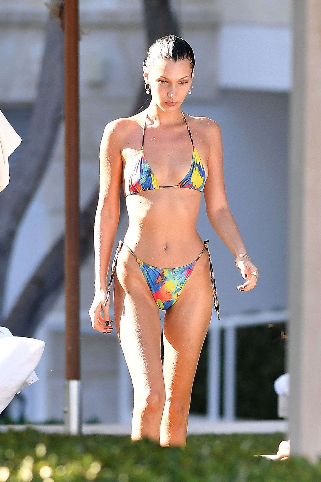 Bella Hadid showcases her phenomenal physique in a tiny rainbow bikini as she soaks up the sun and snacks on fries during a girls' trip to Miami