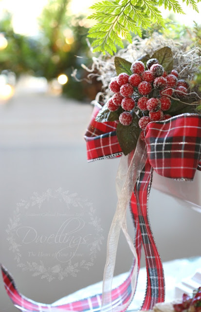 Red berries with a plaid bow dress up an ironstone compote filled with a rabbits foot fern.