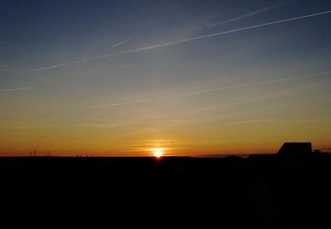 Coucher de soleil rouge et orange, traces d'avions dans le ciel, découpe noire de l'horizon