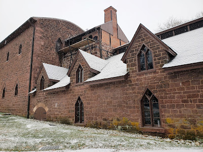Brown stone iron furnace building with gothic windows. Snow covers the roof and the grass next to it.