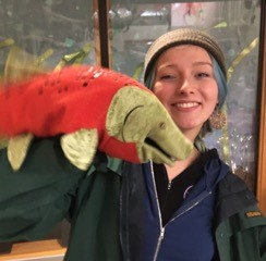 AmeriCorps member Izzi Lavvallee wears a tan headband and carries a large salmon puppet in her right hand.