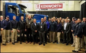 Kenworth employees stand with the first production Kenworth W990