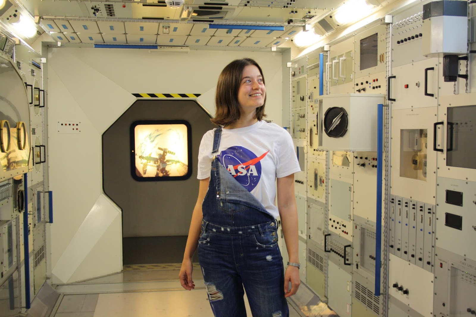 Abbey, wearing a NASA t-shirt and dungarees, stands in a mock-up of a space craft