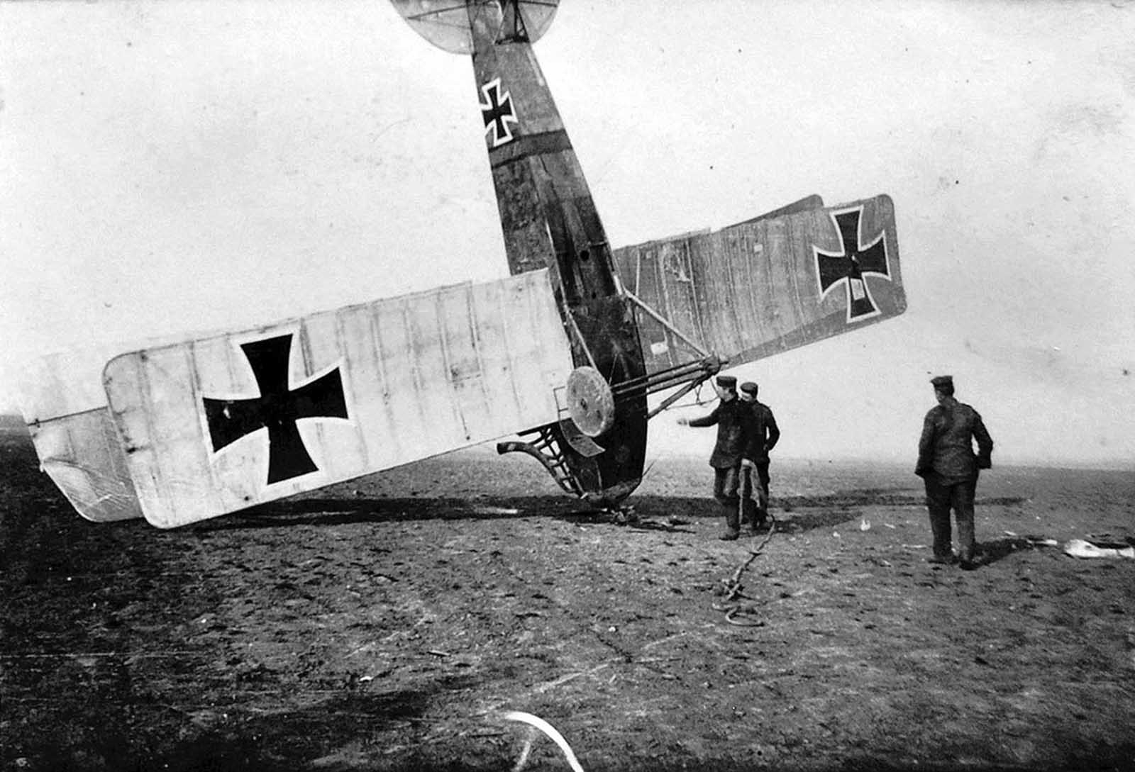 German soldiers attend to an upended German aircraft.