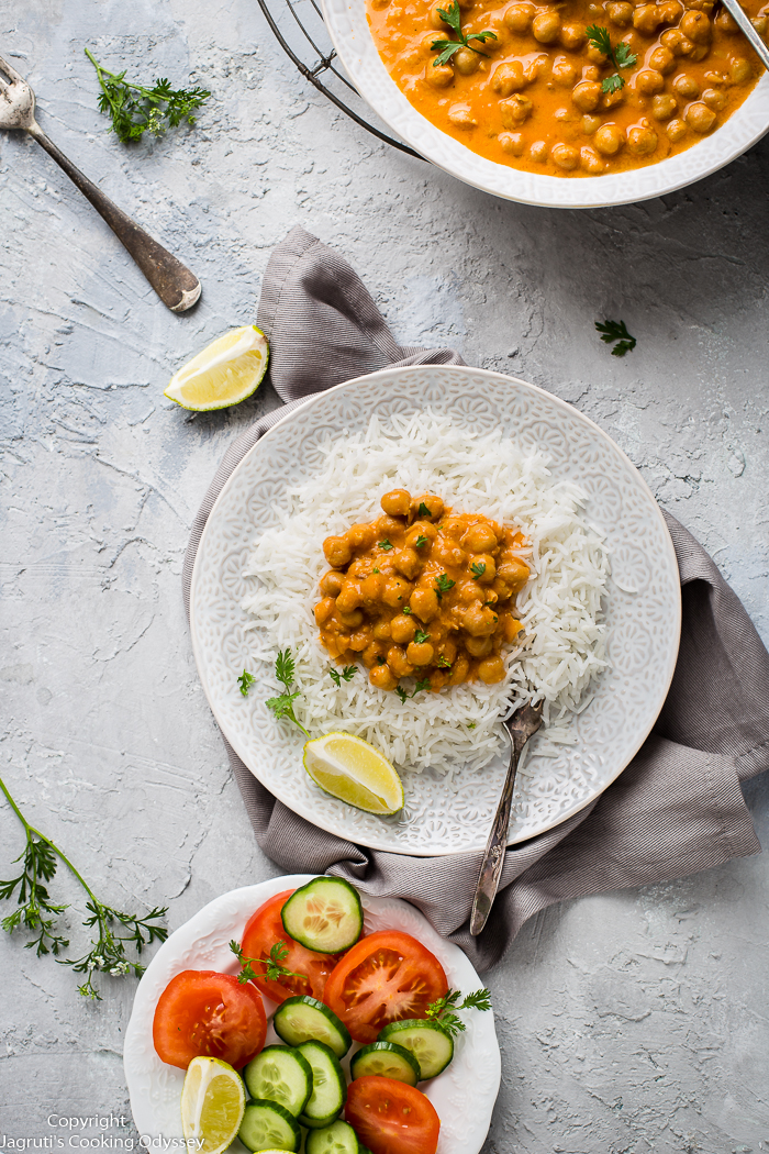image of chickpea curry on a bed of rice with salad