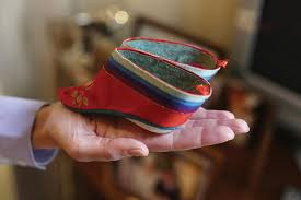 Image of an outstretched, palm holding a tiny pair of  bound shoes in the open palm. The shoes are noticeably smaller than the (small) hand. Photo credit: Smithsonian