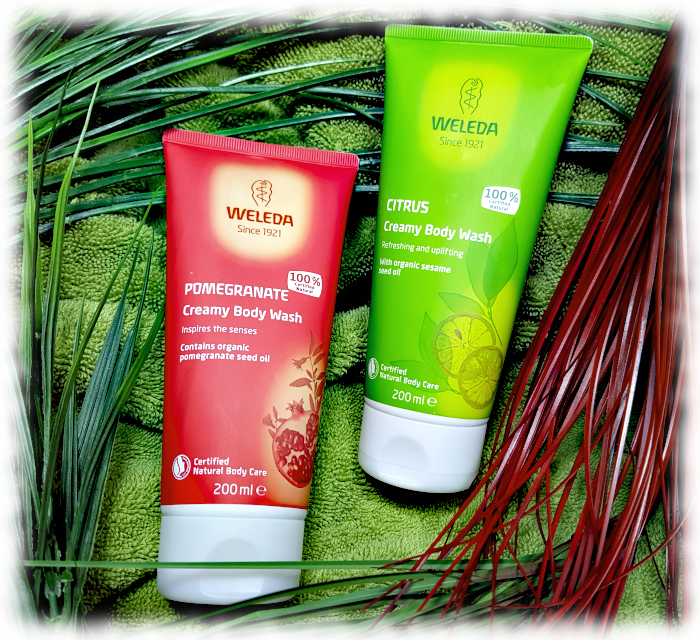 Weleda Pomegranate & Citrus body washes on a towel with spiky plants