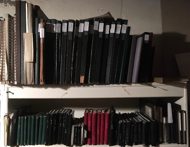 Bookshelf containing numerous sketchbooks of various sizes and colors, many with date labels on spines.""