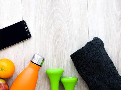 Mancuernas, botella de agua, fruta, móvil y toalla de entrenamiento
