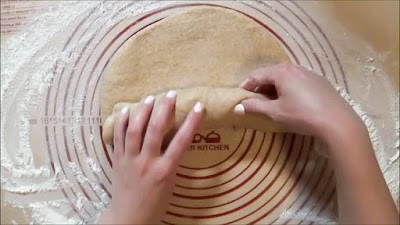 Rolling up wheat bread dough with fingers.