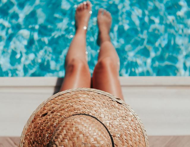 femme au bord de la piscine chapeau de paille