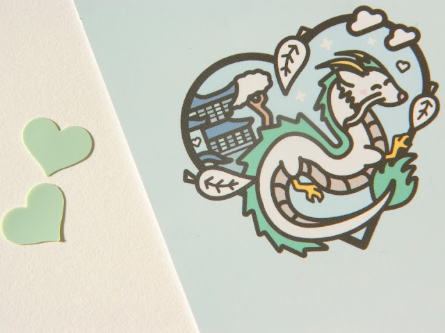 A photo of a business card from Illustrator Jake featuring artwork of Haku the dragon