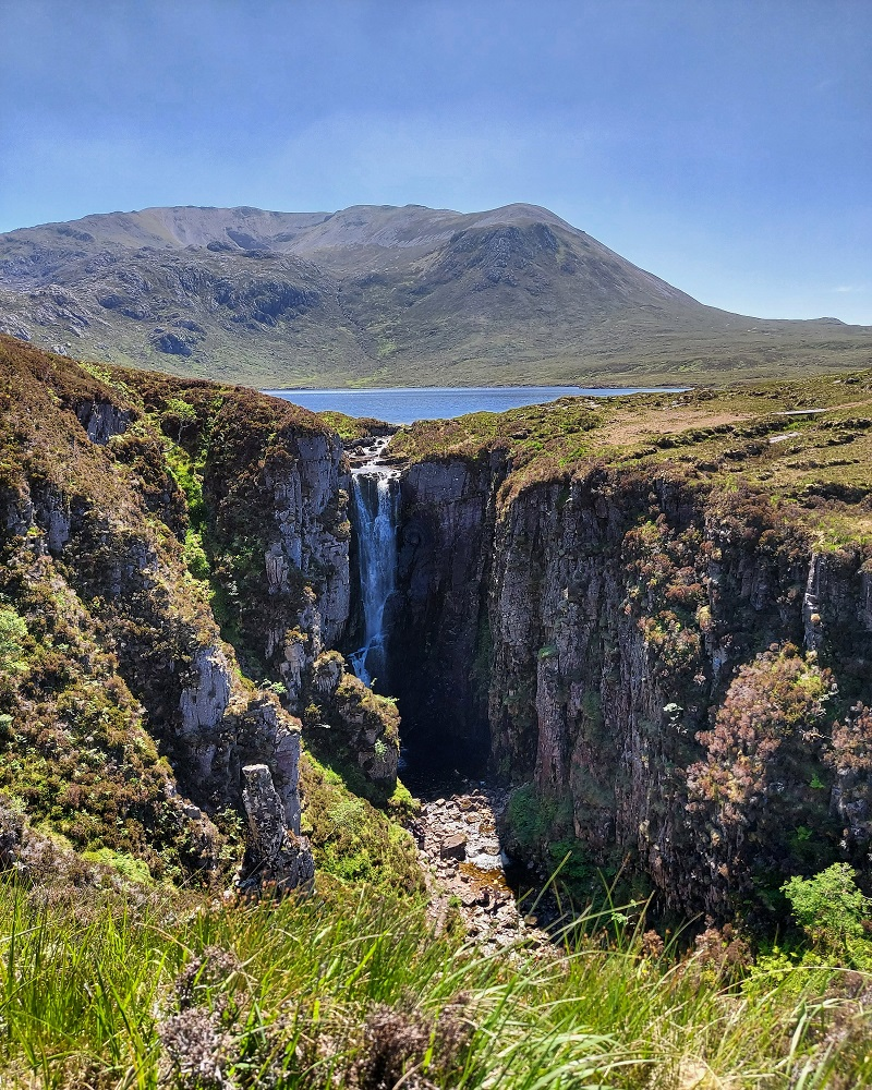 View of wailing widow falls with loch and hills in background