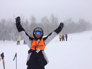 Skier on slope holding up arms and smiling