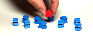 A red meeple is being picked up from a crowd of blue meeples.