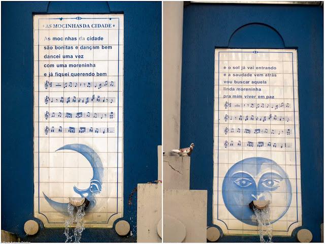 Painel com letra da música na fonte As Mocinhas da Cidade