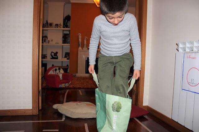 Criança a saltar dentro de um saco reutilizável de supermercado