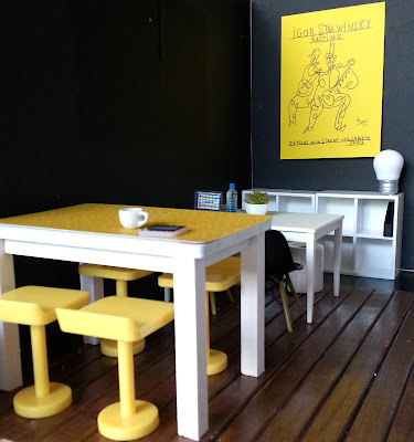 One-twelfth scale modern miniature co-working space, showing two tables (one high, one normal height) lined up and surrounded by seating.