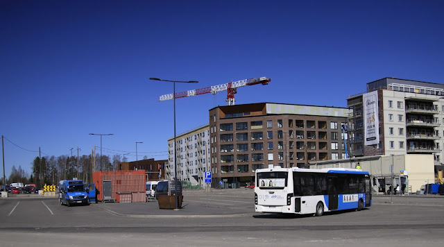 Kuvassa 2 bussia bussiterminaalissa ja muutama matkustaja pysäkillä