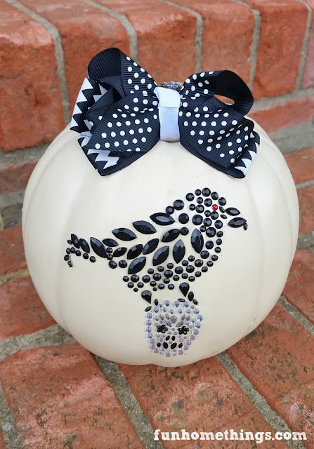 embellished white pumpkin with black decor on porch