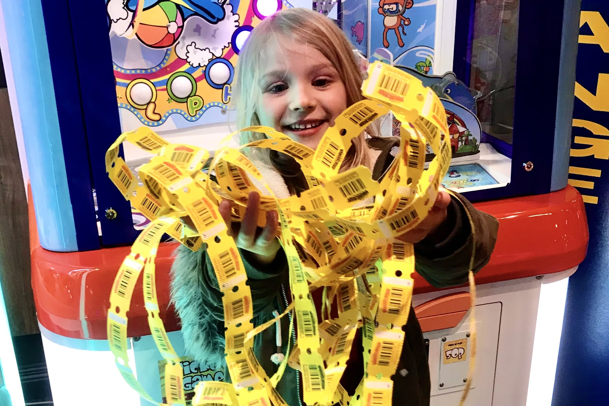 A girl holding an armful of winning tickets from an arcade machine