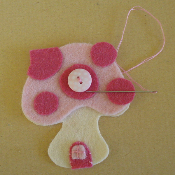Pink button being sewn onto the pink felt mushroom shape