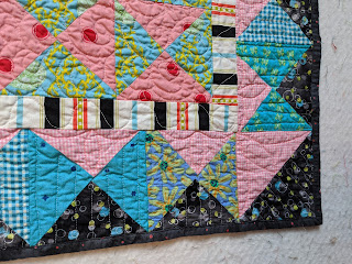 The hourglass border has pink prints to the inside, blue prints on the sides and a black print on the outside to form a strong frame for the quilt