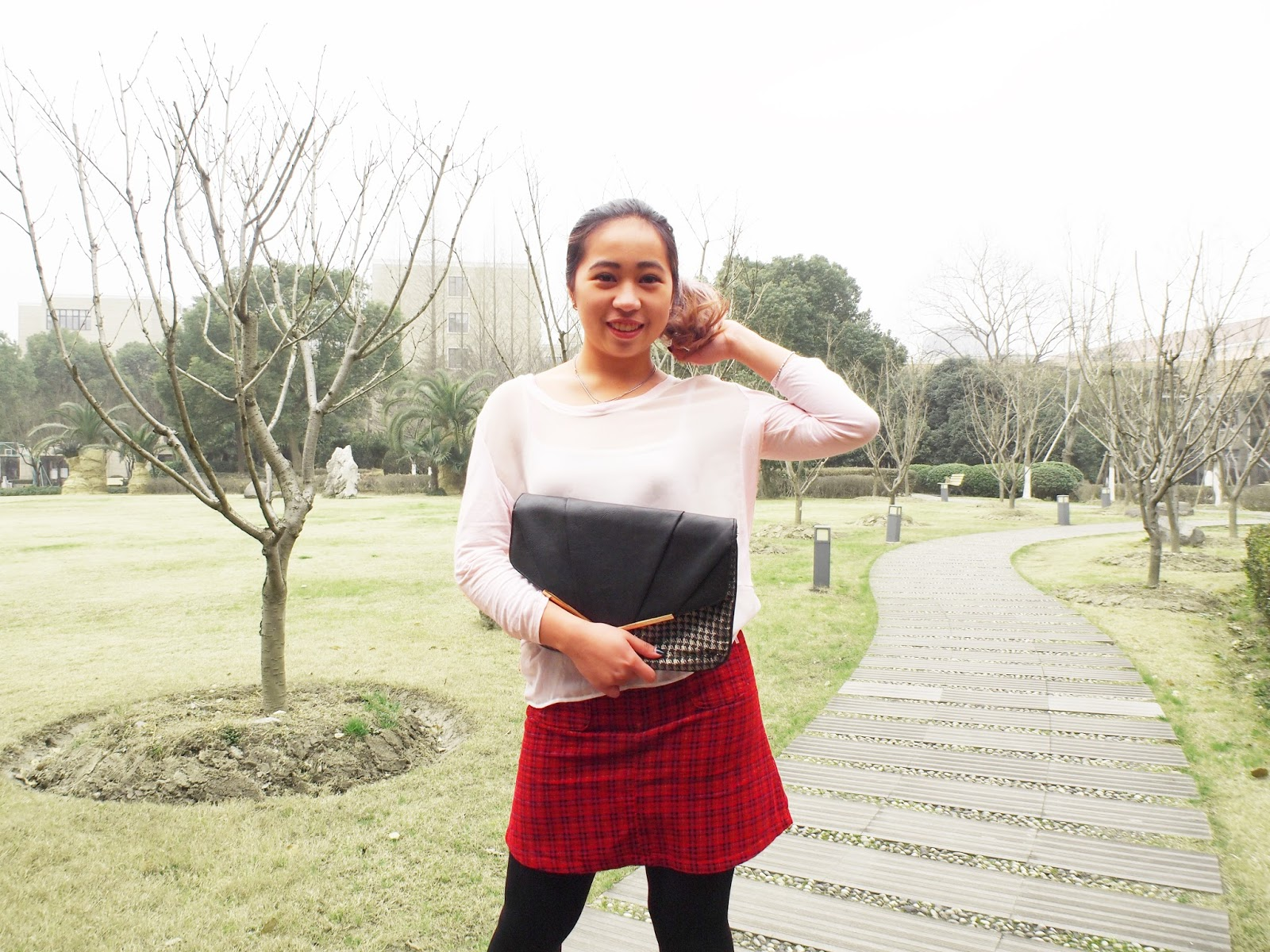 This is a photo of styling a New Look Gold Black Houndstooth Clutch together with Mango Top and Plaid Red Skirt